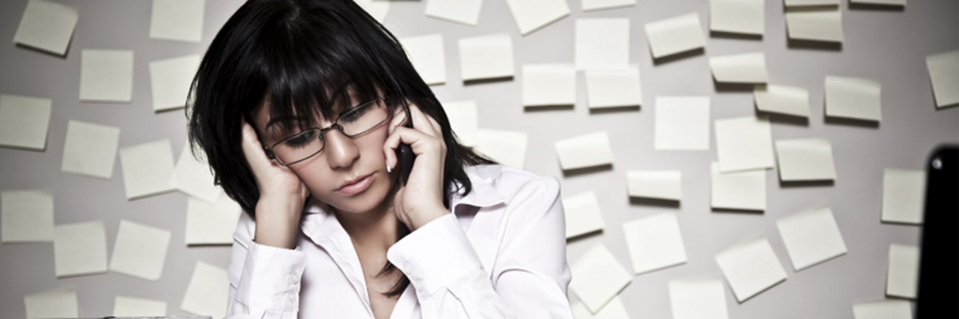 Woman looking overwhelmed with multiple post-it notes in the background